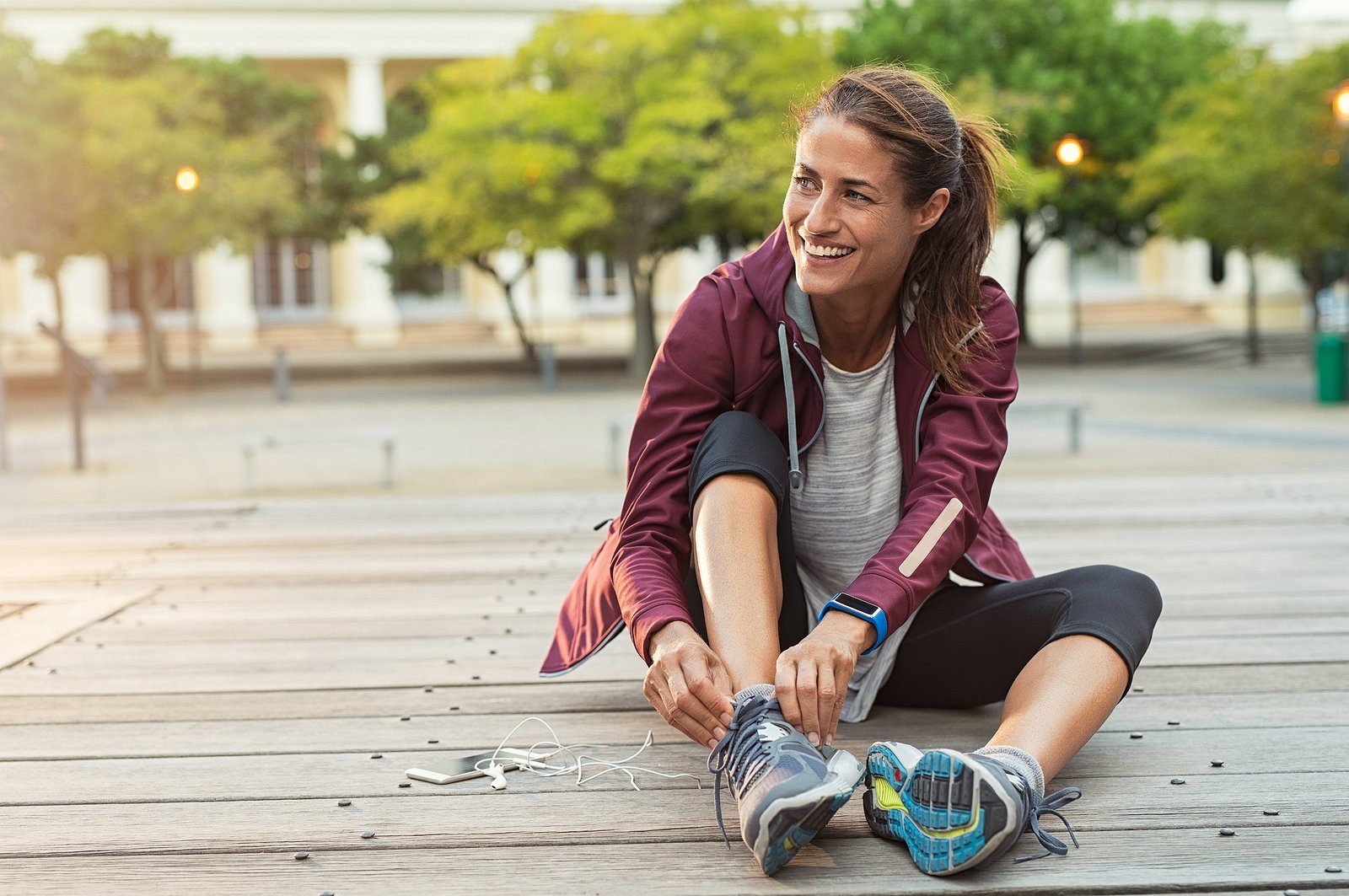 woman pausing while excercising to tie her shoe